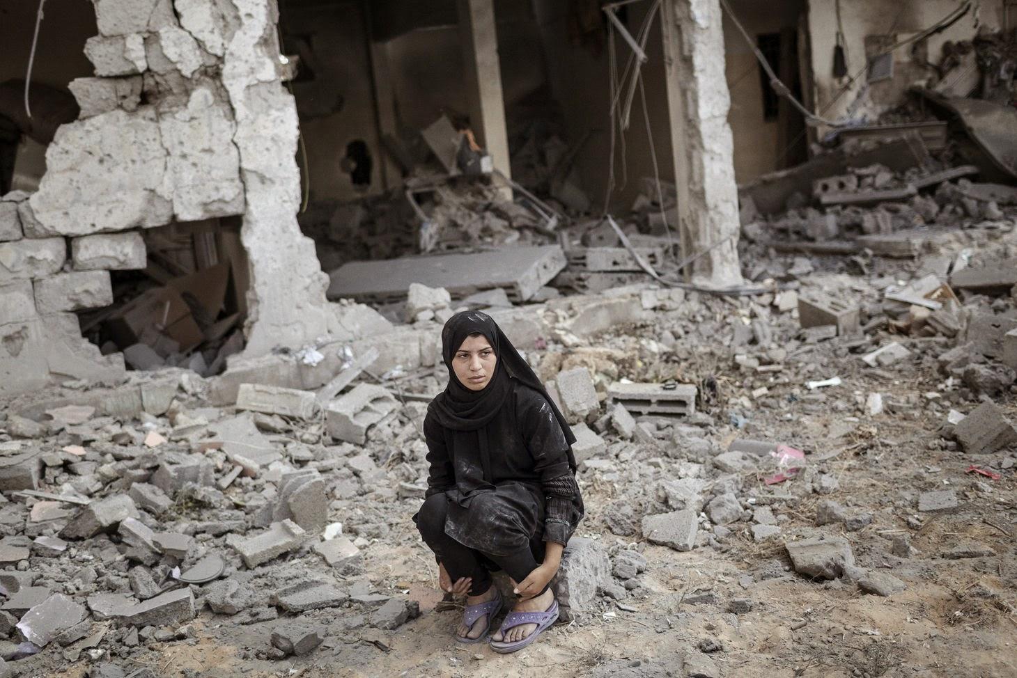 Une femme devant sa maison détruite